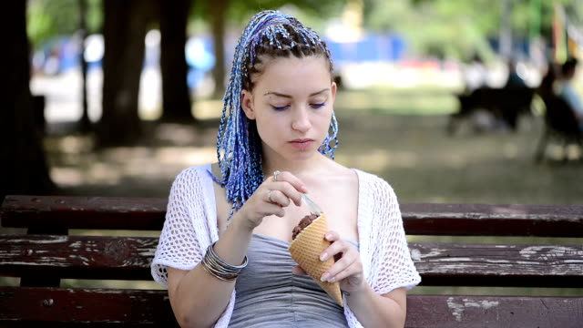Young woman eating ice cream sitting on a bench in the park video