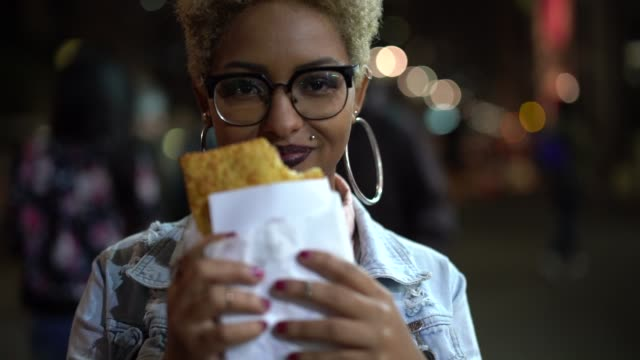 Young Woman Eating Pastel on the Street After Work