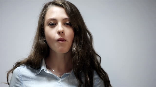Young woman eating potato chips at gray background video