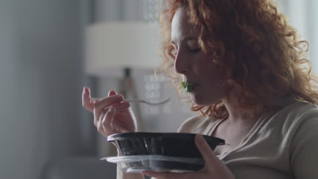 Young woman eating take out food for lunch at home Headshot of young woman sitting in a chair at home, opening a container with take out food and enjoying eating her salad. fork stock videos & royalty-free footage