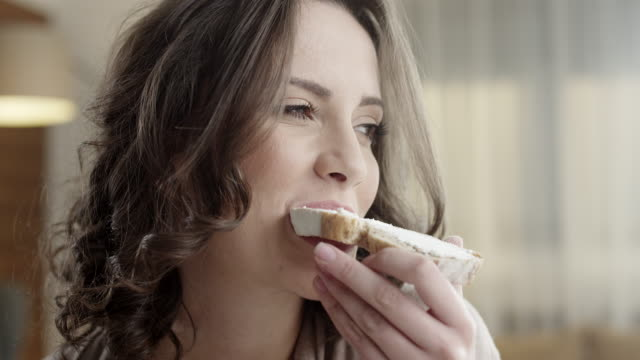 Young woman eating Young happy woman eating breakfast bread stock videos & royalty-free footage