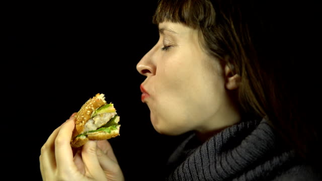 Young woman eats a burger on a black background video