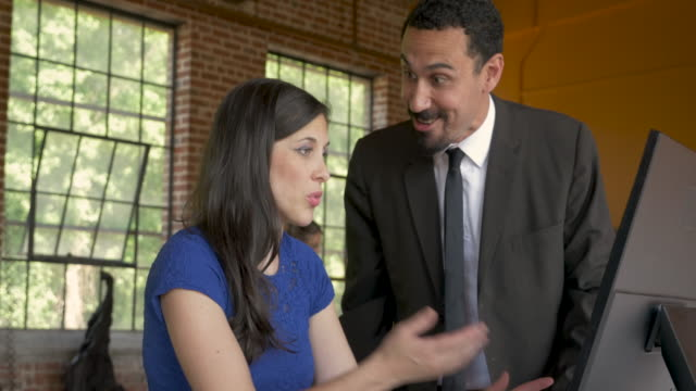 Young woman employee trying to explain herself to her angry boss