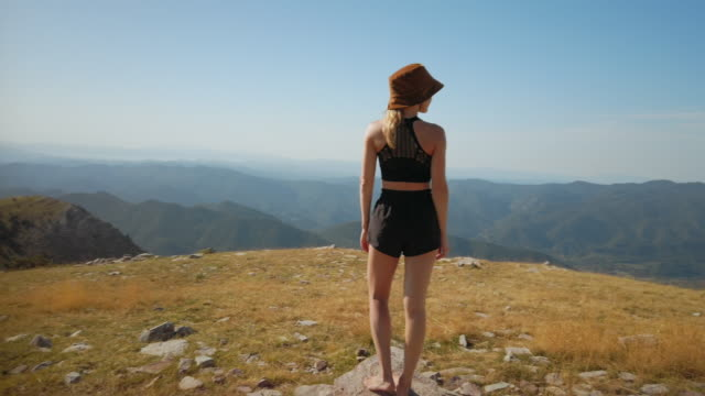 junge frau genießen blick über bergtal - hochplateau stock-videos und b-roll-filmmaterial
