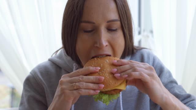 vídeos de stock, filmes e b-roll de jovem, desfrutando de um hambúrguer grande em casa - comida feita em casa
