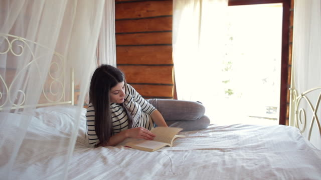 Young woman enjoying a book in bed. video