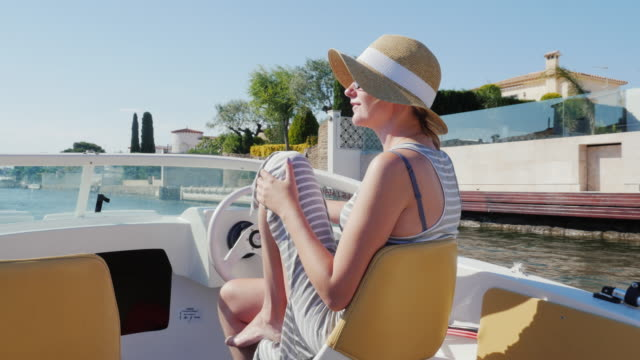 Young woman enjoying a holiday on the European resort. Floating on a boat on the channel Empuriabrava, Spain video