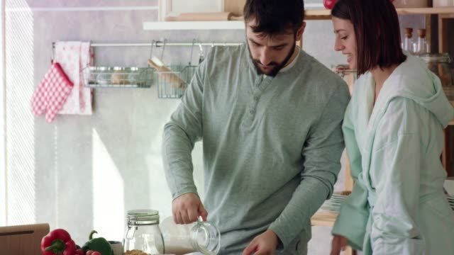 young woman enjoying a sip of coffee while her boyfriends is preparing cereal for breakfast - pajamas stock videos & royalty-free footage