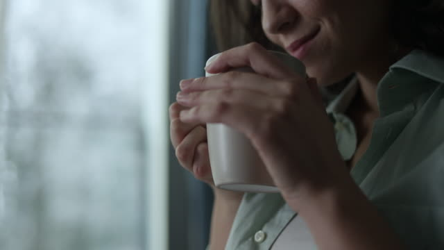 Young woman enjoying coffee Young happy woman enjoying coffee in the morning mug stock videos & royalty-free footage
