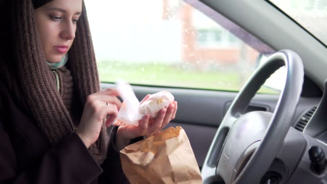 Young woman enjoying eating a burger in the car video