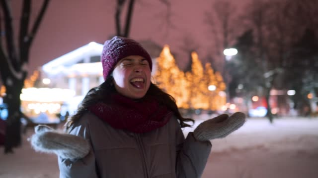 Young woman enjoying falling snow outdoors on winter night at Christmas market. Happy girl open arms under snowfall in park and catch the snowflakes with hands, mouth. Female stretch out arms to sky