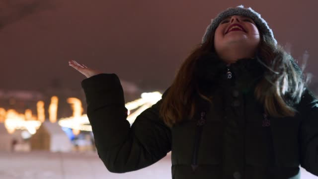 junge frau genießt fallenden schnee im freien in der winternacht auf dem weihnachtsmarkt. glückliches mädchen offene arme unter schneefall im park und fangen die schneeflocken mit händen, mund. weibchen strecken arme zum himmel aus - girlande dekoration stock-videos und b-roll-filmmaterial