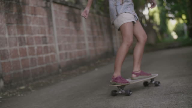 Young woman enjoying goes longboard skateboarding