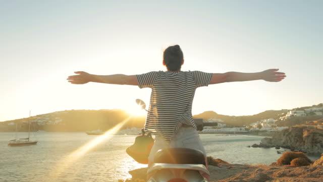 vidéos et rushes de jeune femme à profiter de ses vacances avec moteur scooter. - femme seule s'enlacer