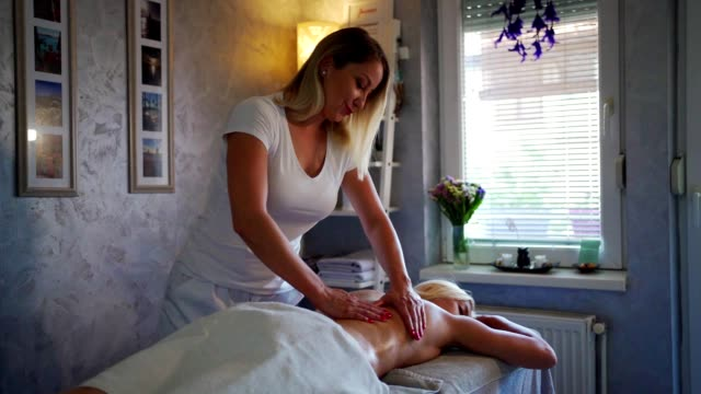 Young woman enjoying in relaxing massage Woman laying on the table while female masseur massaging her back. massage oil stock videos & royalty-free footage