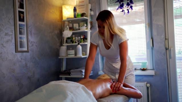 vídeos y material grabado en eventos de stock de joven mujer disfrutando en masaje relajante - espalda humana