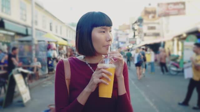 Young Woman Enjoying Mango Juice in Khao San Road. Bangkok,