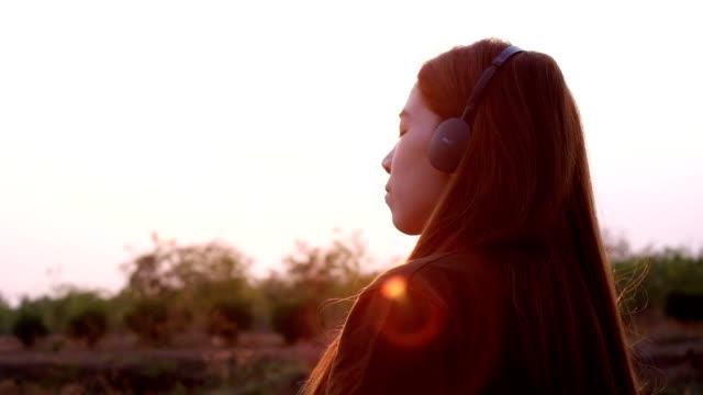ung kvinna njuter av musik i solnedgången - ligga på mage bildbanksvideor och videomaterial från bakom kulisserna