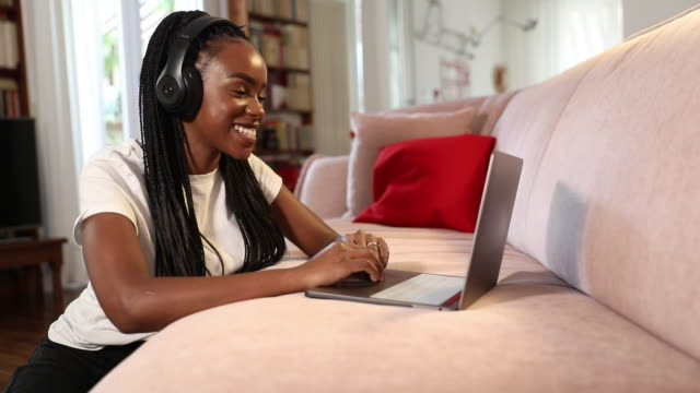 Young woman enjoying music in the living room sitting on the floor video