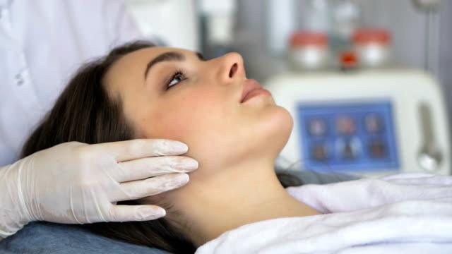Young woman enjoying of facial massage in beauty salon video