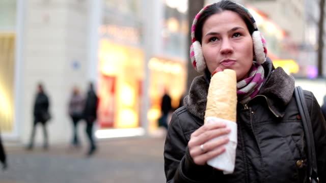 Young woman Enjoying street food in winter video