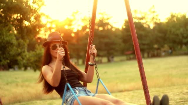 若い女性スイング夏の夕日をお楽しみいただけます。 - 春のファッション点の映像素材/bロール