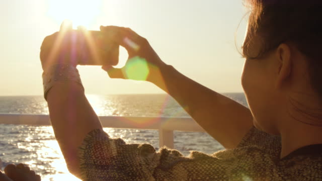 Young woman enjoying sunrise on travel at sea. Taking pictures of the ocean on a ferry on cruise ship vacation