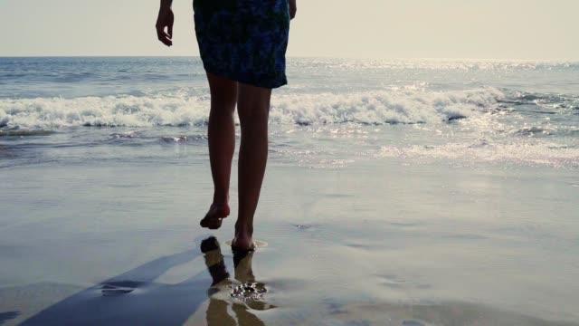 ung kvinna njuter av havet. leka med vågor - spain solar bildbanksvideor och videomaterial från bakom kulisserna