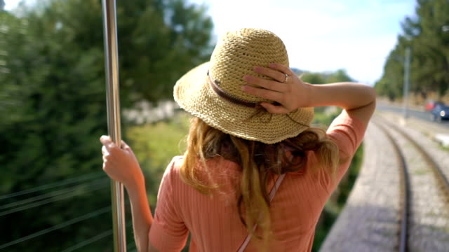 A young woman enjoying traveling on an old train, admiring beautiful tourist locations A young woman wearing straw hat enjoying traveling on an old tram or train, admiring beautiful southern tourist locations, feeling excited and happy charming stock videos & royalty-free footage