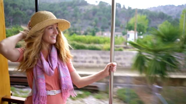 a young woman enjoying traveling on an old train, admiring beautiful tourist locations - сбежавший из дома стоковые видео и кадры b-roll
