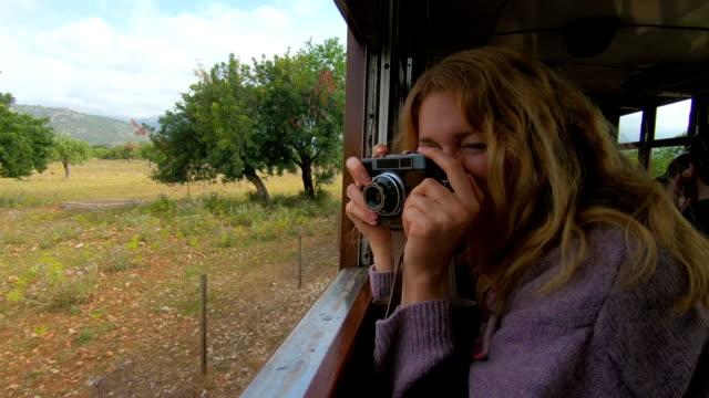 a young woman enjoying traveling on an old train - ekoturystyka filmów i materiałów b-roll