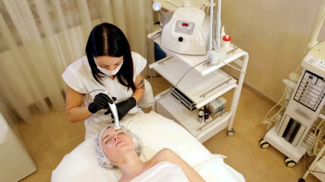 A young woman enjoys a mesotherapy procedure in a Spa salon. View from the top. A young woman enjoys a mesotherapy procedure in a Spa salon, she lies on a cosmetology table with her eyes closed and covered with a towel. Facial massage in the beauty salon. dermatology stock videos & royalty-free footage
