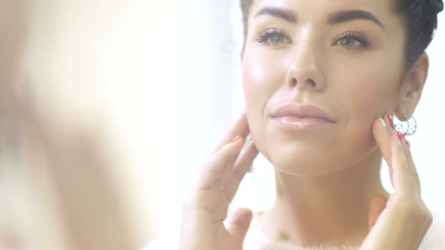 Young woman enjoys her clean skin looking in the mirror video