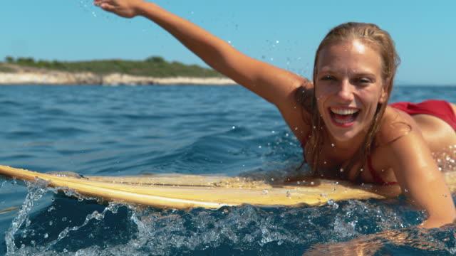 초상화: 젊은 여성은 완벽한 여름 날에 서핑을하며 휴가를 즐깁니다. - 젊은 여자 스톡 비디오 및 b-롤 화면