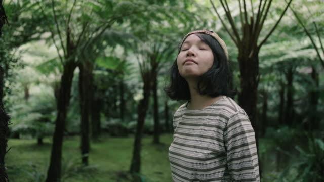 若い女性を楽しんでリラックスして彼女を取り巻く森のビューで。 - 日常から抜け出す点の映像素材/bロール