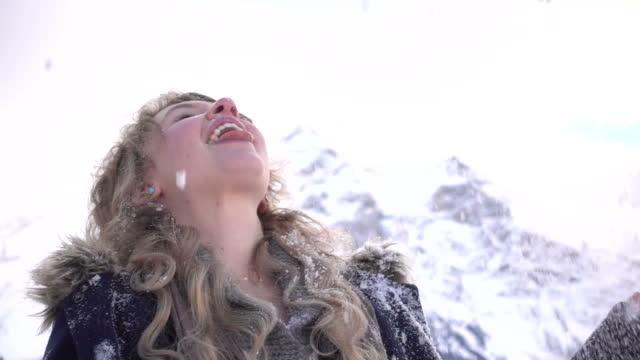 la giovane donna ama i fiocchi di neve, l'ambiente invernale di montagna - fare la lingua video stock e b–roll