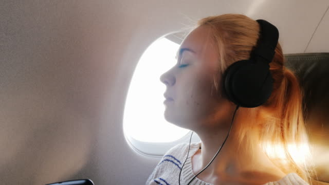 Young woman enjoys the flight, listening to music video