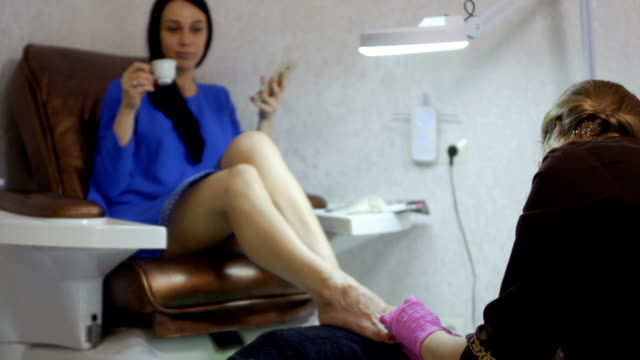 young woman enjoys the procedure of making pedicure in salon - pedicure filmów i materiałów b-roll