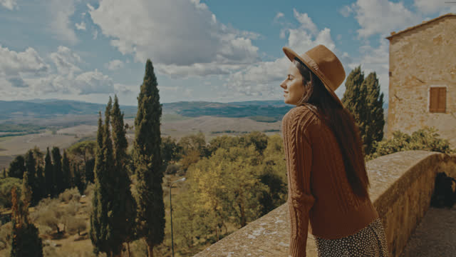 SLO MO Young woman enjoys the view from the city walls at Pienza