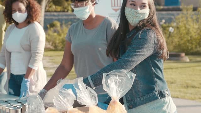 푸드 드라이브 중 친구들과 자원봉사를 즐기는 젊은 여성 - giving tuesday 스톡 비디오 및 b-롤 화면