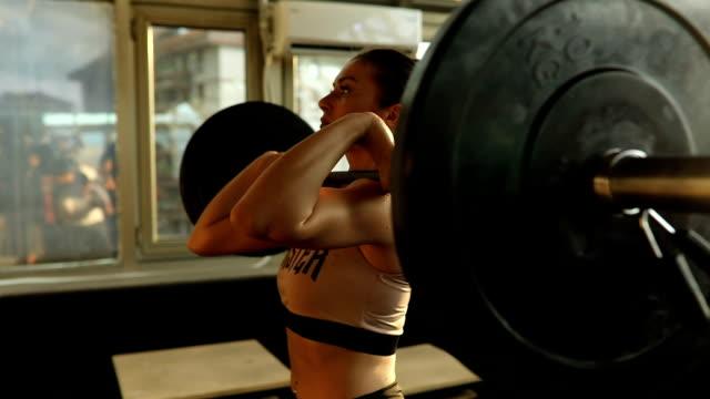 vídeos de stock e filmes b-roll de young woman exercise with barbell in gym - agachar se
