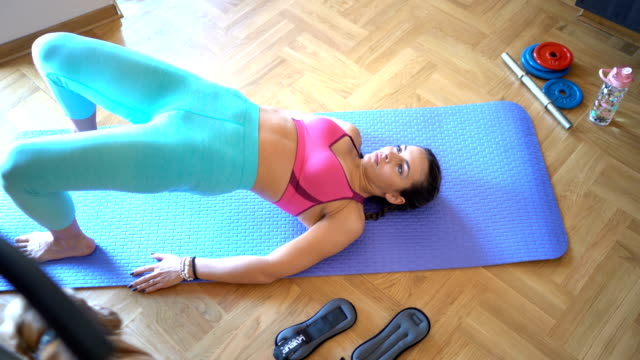 Young woman exercises on floor video