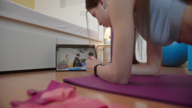 junge frau trainiert zu hause - fitnesskurs stock-videos und b-roll-filmmaterial