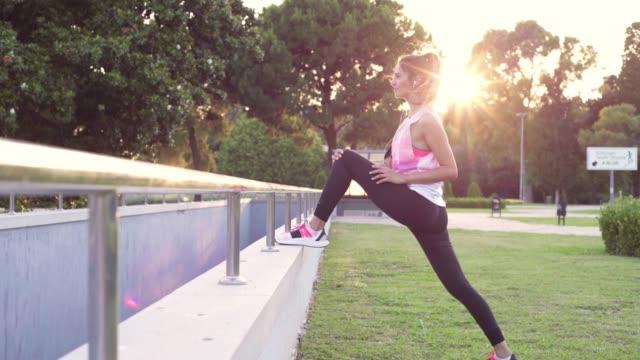 young woman exercising in public park - rozgrzewka filmów i materiałów b-roll