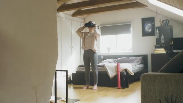 ung kvinna tränar med vr-headset hemma - endast en ung kvinna bildbanksvideor och videomaterial från bakom kulisserna