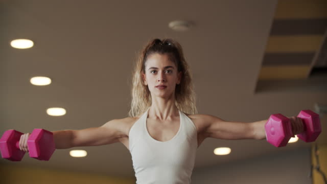 ダンベルで運動する若い女性は体重を持ち上げる - 支えられた点の映像素材/bロール
