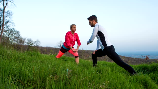 Young woman exercising with personal fitness instructor outdoors video