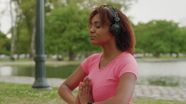 Ung kvinna som tränar yoga i en offentlig Park video