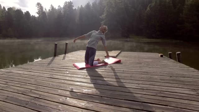 4k, young woman exercising yoga in nature, switzerland - gente serena video stock e b–roll
