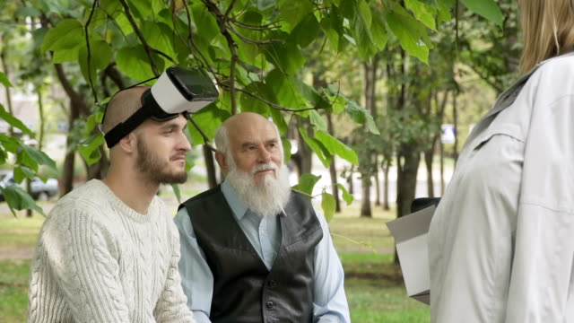 Young woman explain something to man in virtual reality glasses and old man video